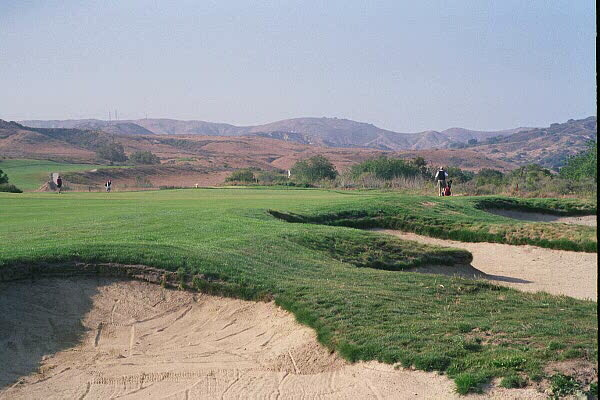 The golfer looks straight down the 40 yard long rectangular 10th green by staying close to these bunkers.