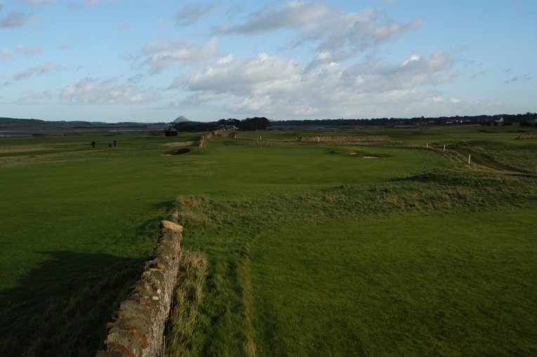 The tees are on the left and the green is to the right of this former boundary wall.