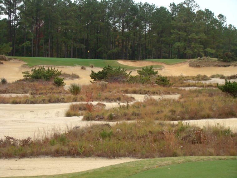 The direct line to the green is a carry of 230 yards to clear the sand and 260 yards to reach the putting surface.