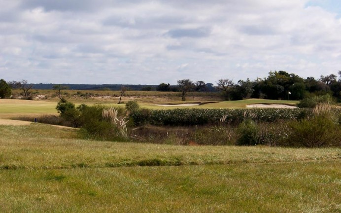 The view is from the twelfth tee with the white flag acting as a siren, wooing the golfer into potential trouble. If able to resist, the smart golfer hits straight down the fairway, leaving himself a relatively simple pitch and a chance for birdie. Conversely, one mighty blow and the golfer may be putting for eagle...
