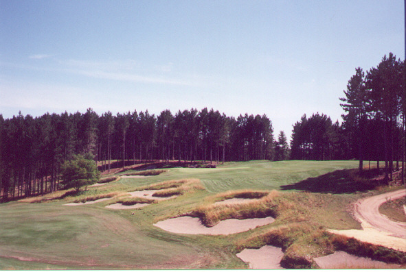 16th hole, 215 yards: A friendly version of the Redan hole, the 16th green occupies part of a moderate hillside that is just level enough to stop golf balls. While many Redans have a drop-off to the right of the green, this version offers more than 30 yards of fairway to the right, tumbling down the hill essentially into the green. A player can therefore play a hook that lands a full 20 yards right of the green and then have the satisfaction of watching his ball chase down the hill and onto the green. The length of the hole encourages players to use that tact, as the hole would be less interesting with, say, a 7-iron in hand rather than a 3-iron. Also, while standing on the tee, the player plays directly across the bunkers well left of the 15th green. The bunkers 'look' as though they belong on each hole, testimony to the thought that went into the design and shaping.