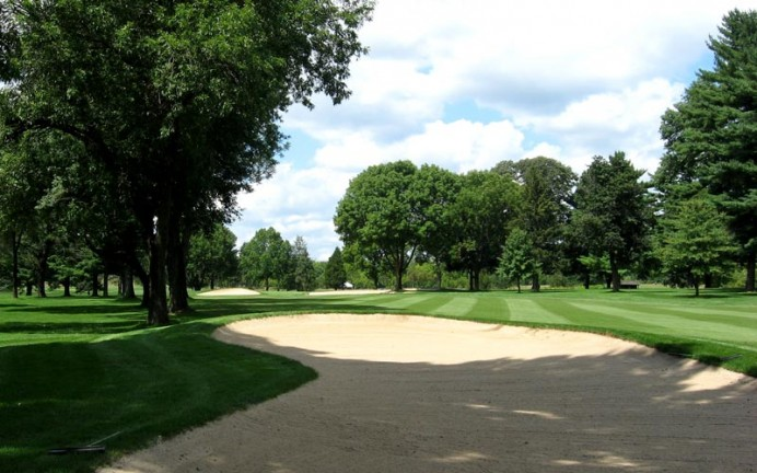 Former  Church Pews face the unbroken stand of trees that march down the left edge of the seventh fairway and overhang the direct route to the green.