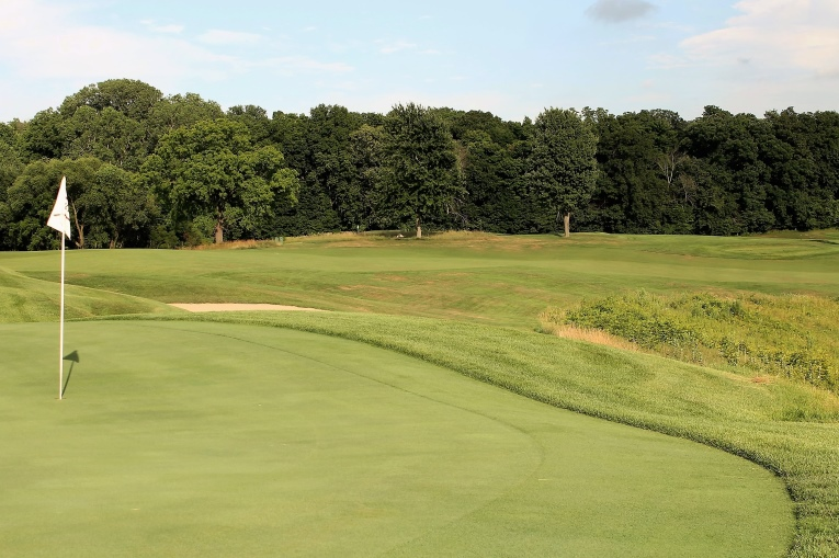 Some might wonder how nine holes that measure 3,230 yards can challenge good players. The depth of the hazards and the green contours are two immediate answers. Additionally, several tee balls like the one here hit into upslopes and kill much roll. Also, given that the best angle into the 4th green and most level stances are afforded from the outside of the dogleg, the hole plays longer than its 370 yards.