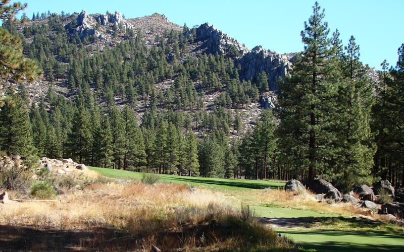 A towering rock formation serves as the backdrop to the tee ball before the fairway swings….