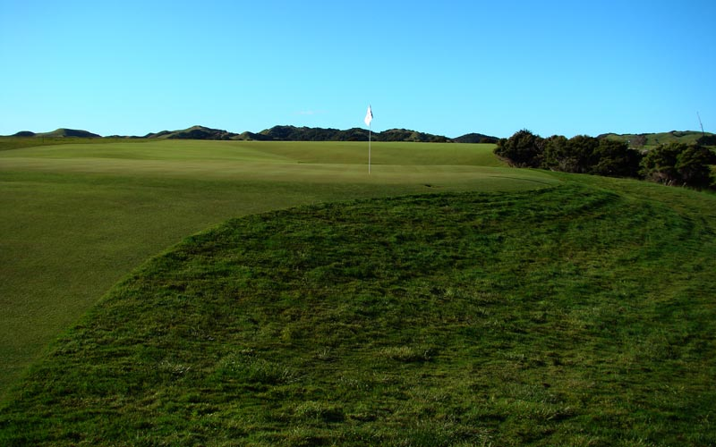 The golfer is frequently rewarded for playing bold attacking golf. As this view from behind the twelfth green indicates, even if he is a bit aggressive with his approach shot, he has a chance to recover. Notice how much of the putting surface is in view from behind the green, a sure sign that the green slopes from front to back.