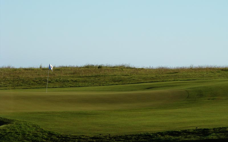 The firm playing surfaces on offer at Cape Kidnappers provide the golfer a range of options. Here at the ninth, should he take dead aim at the flag or use the short grass to the high right side of the green to feed his approach shot close?