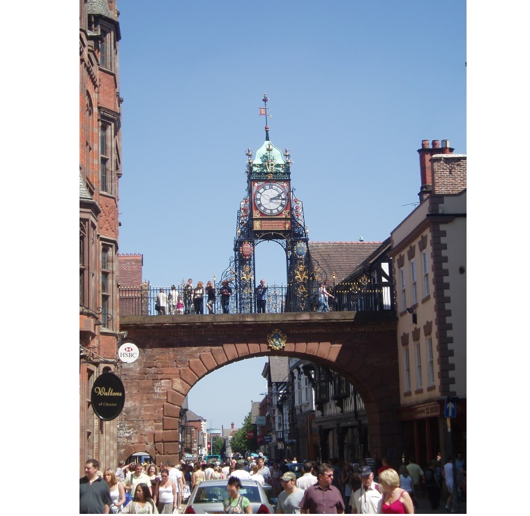 Visitors, walking the walls of Chester, look down on shoppers in Eastgate Street. The clock was erected for Queen Victoria's Silver Jubilee in 1897.