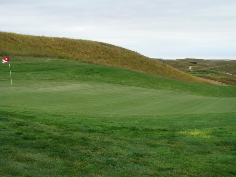 Simple from behind - the green, the hill that obscures it and the tee (underneath Jack's Shack in the far distance).