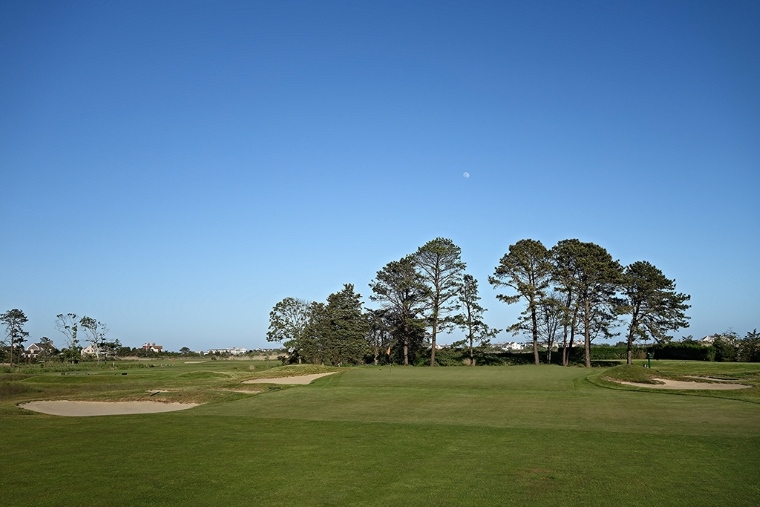 "When the green first comes into view after a slight left turn in the fairway, the golfer encounters a feature that repeats throughout the course: an open-front green, at grade, with ""squared up"" elements that allow for low, wind-skirting, run-up shots—a regular necessity on a course as exposed to the wind as Quogue. These inviting features, together with the pushed-up backs, evoke comparisons to the greens built around the same time by Bendelow's contemporary and fellow Scot Donald Ross."