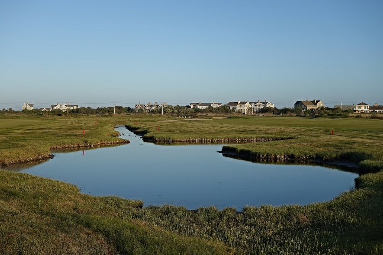 Consistent with Bendelow's hands-off design philosophy, the water hazards at Quogue—like this inlet from the bay running between the 5th and 6th holes—are found, not built. The Atlantic Ocean lies just beyond the homes in the distance.