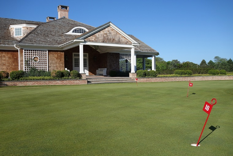 While more subtle than the Himalayas at St. Andrews or the Punchbowl at Bandon Dunes, QFC's practice putting green, with the club's flagpole at its center, has 18 holes with correspondingly labeled iron flag sticks.