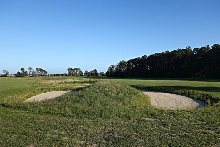 Where trees used to separate the 1st fairway (to the right) and the 9th fairway (to the left), bunkers now sit. Here, a dual-sided bunker encountered after crossing Quaquanantuck Road, which bisects the adjacent fairways and allows passersby to gaze upon the course. The dark stand of trees on the right is out of bounds, which lines the first 350 yards of Quogue's opener. Although the playing corridors and green open up from the right side, the out of bounds makes it a risky target from the tee.