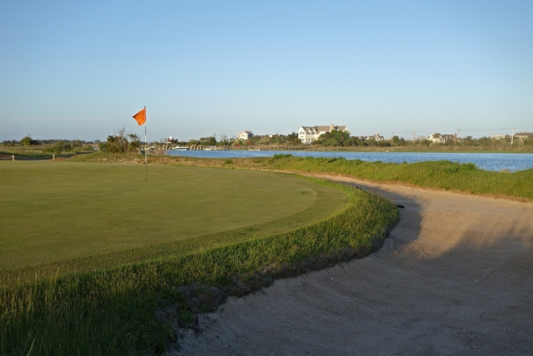 The battle isn't over once the golfer reaches the green, where a small false front, as well as a bisecting ridge, must be navigated. Approach shots hit long or right have a chance of being kept from the bay by another well-positioned rear-guard moat bunker.