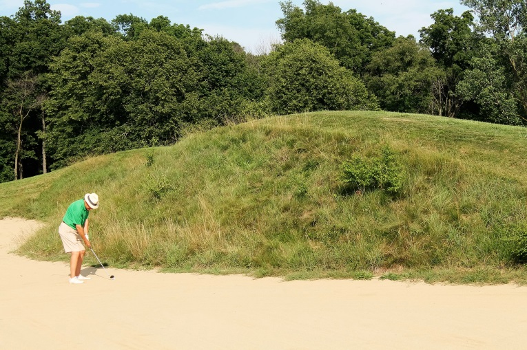 Alas, this six foot two inch tall gentleman's second shot didn't quite clear the bunker built on the crest of the hill. If it had, it could have tumbled all the way ...