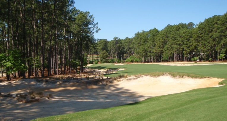 The 12th at Mid Pines as it sweeps left to a green that is angled from front left to back right.