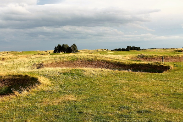 The fluttering yellow flag ahead indicates the hole's typical right to left breeze, the very conditions that love to shove one's tee ball into one of these bunkers on the inside of this dogleg left.