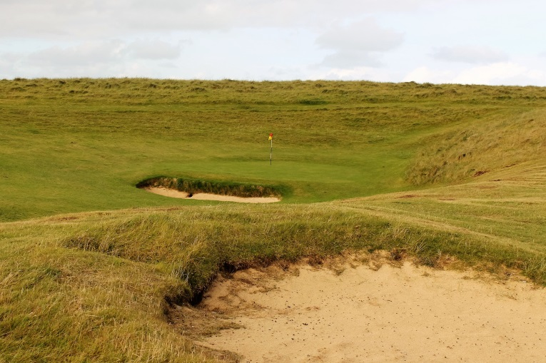 ... two hidden bunkers 40 yards shy of the green as well as a small pit that fronts the green on the direct line from the tee. Trail and error suggests there is wisdom in playing short left of the green and tacking in from there.