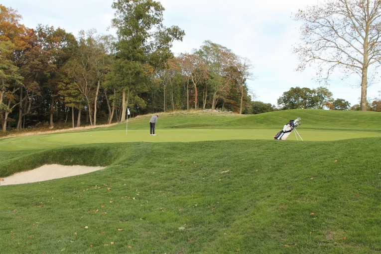 The golf bag provides a sense of today's four foot drop from back to front on the seventh green.